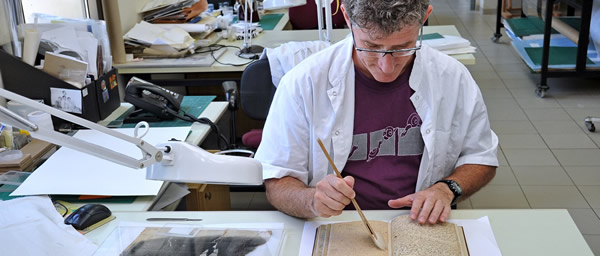 Yuval Sitton, a paper conservator at Yad Vashem, is dry-cleaning a Holocaust-era diary in the paper conservation lab. Photo Yad Vashem